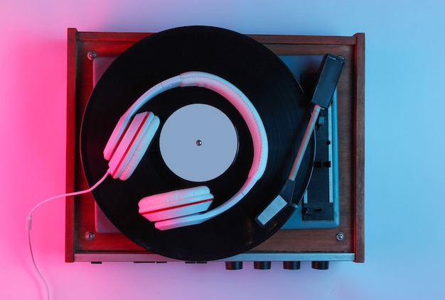 Retro style music concept. classic headphones, vinyl record player with gradient pink-blue neon light. pop culture. 80s. top view