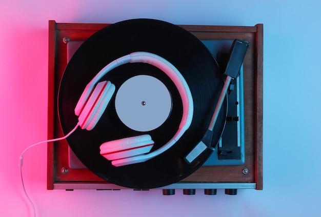 Музыкальная концепция в стиле ретро. классические наушники, виниловый проигрыватель с градиентным розово-голубым неоновым светом. популярная культура. 80-е гг. вид сверху