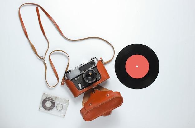 Ретро стиль фона ностальгии. ретро фотоаппарат в кожаном футляре с ремешком, виниловая пластинка, аудиокассета на белом фоне.