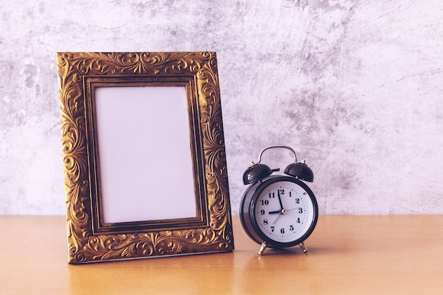 Retro style picture frame and alarm clock on wooden table.