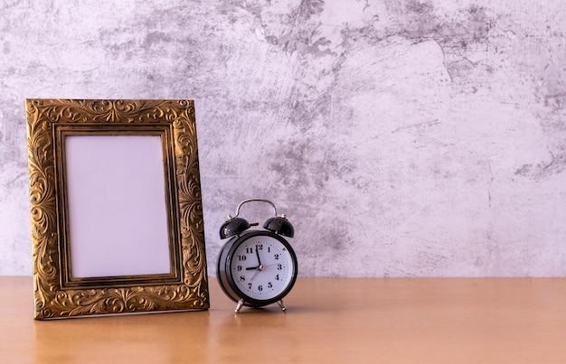 Рамка для фотографий в стиле ретро и будильник на деревянном столе