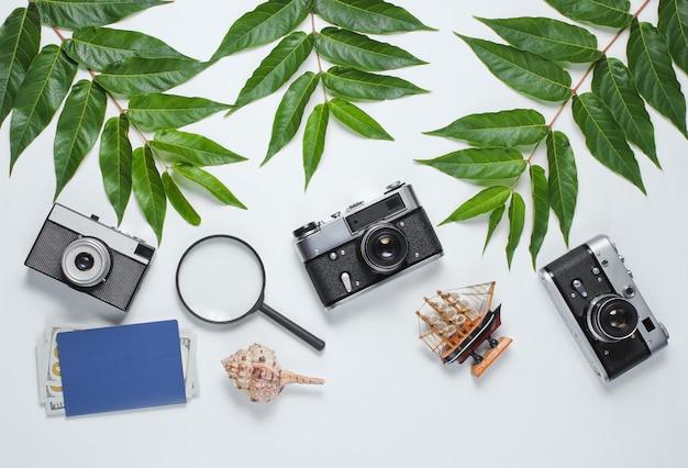 Ретро-стиль путешествия натюрморт. пленочный фотоаппарат, снаряды, зеленые тропические листья. аксессуары для путешественников на белом фоне. вид сверху