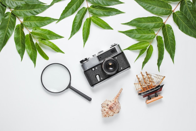 Retro style travel still life. film camera, shells, green tropical leaves. traveler accessories on a white background. top view