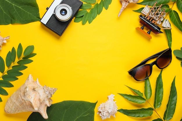 レトロなスタイルの旅行静物。フィルムカメラ、サングラス、貝殻、緑の熱帯の葉。黄色の背景に旅行者のアクセサリー。