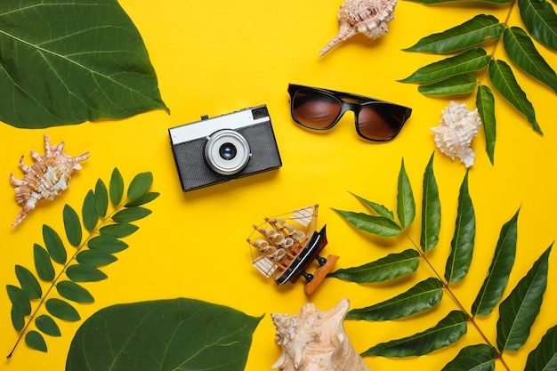 Retro style travel still life. film camera, sunglasses, seashells, green tropical leaves. traveler accessories on yellow background.