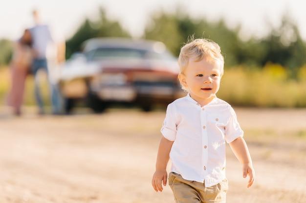 レトロなスタイル。ユニークな車。両親は後ろの車の近くに立っており、息子は前景で彼らから逃げて遊ぶ