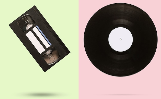 パステルカラーの背景にレトロなスタイルのビデオカセットとビニールレコード