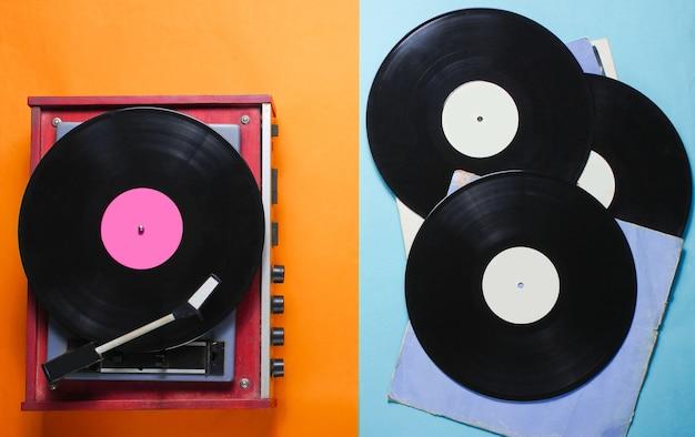 レトロなスタイルのビニールレコードプレーヤーと色紙にカバー付きのビニールレコード