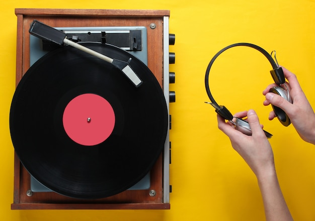 Retro style, vinyl record player and hand holds headphones, minimalism, top view on yellow background, 80s