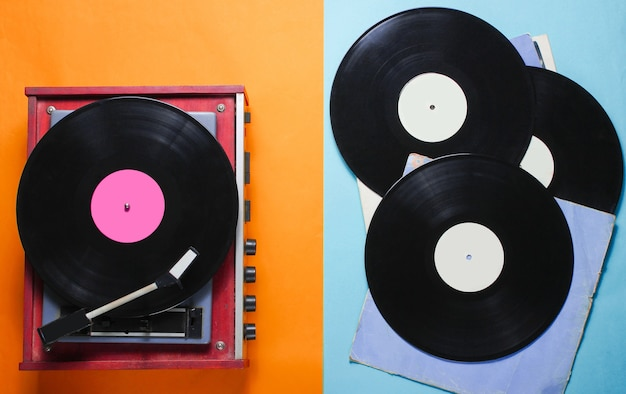 Retro style vinyl record player and vinyl records with covers on a colored paper