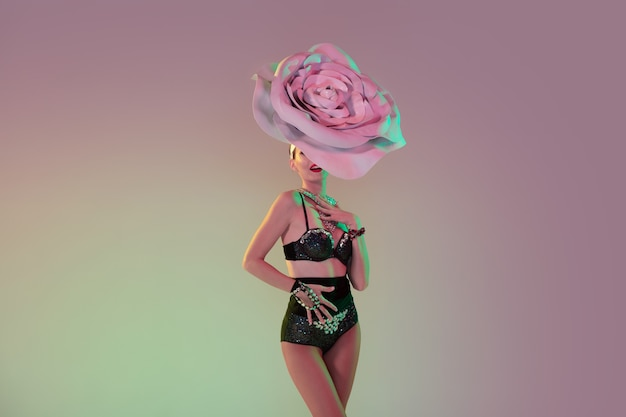 Retro style. young female dancer with huge floral hats in neon light on gradient wall. graceful model, woman dancing, posing. concept of carnival, beauty, motion, blooming, spring fashion.