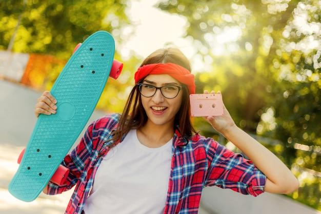 복고풍 스타일의 청소년 모습. 80 년대. 세련 된 옷에 젊은 매력적인 힙 스터 여자는 밝고 화창한 날에 skatepark에서 카메라에 포즈를 취하는 동안 스케이트 보드와 오디오 카세트를 보유