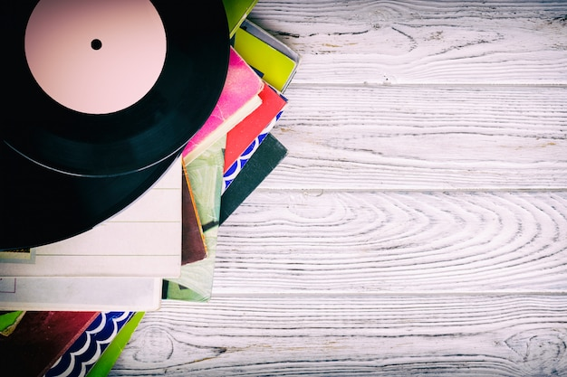 Retro styled image of a collection of old vinyl record lp's with sleeves on a wooden background with copy space top view toned