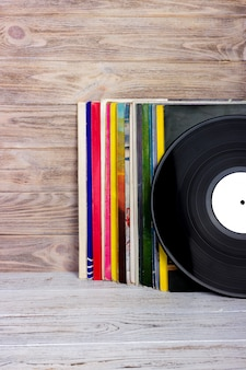 Retro styled image of a collection of old vinyl record lp's with sleeves on a wooden. copyspace.
