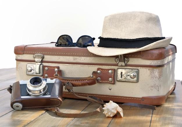 밀짚 모자와 안경 흰색 나무 테이블에 레트로 가방과 카메론 펀트