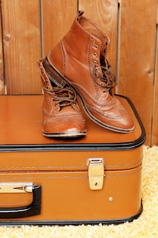 Retro suitcase with male shoes on fur carpet and space