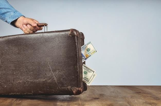 男の手にお金とレトロなスーツケース