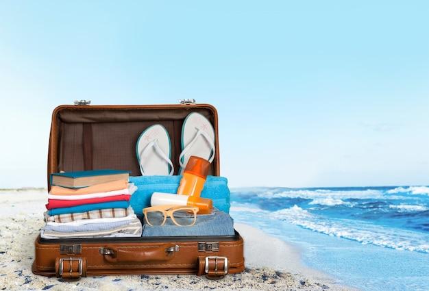 호텔 배경에 여행 물건이 있는 복고풍 가방