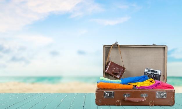 바다 배경에 여행 개체와 레트로 가방