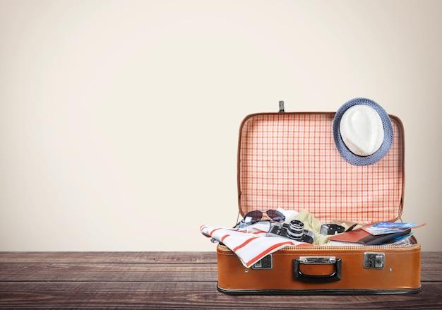 바다 배경에 여행 물건이 있는 복고풍 가방