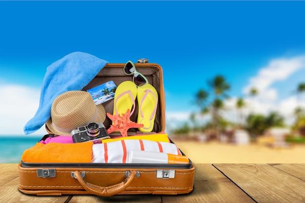 해변 배경의 나무 책상 위에 여행 물건이 있는 복고풍 가방
