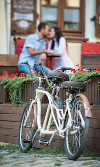 Retro tandem bicycle near red flowers. couple kissing