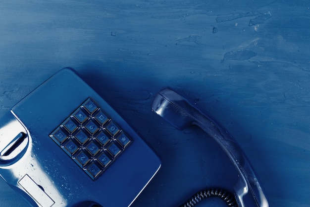 Retro telephone of blue color on classic blue background