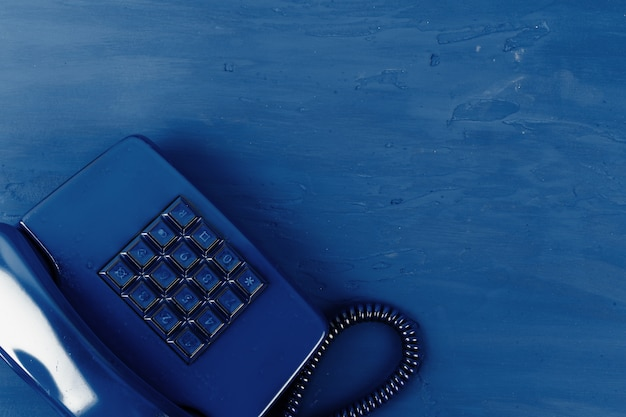 Retro telephone of blue color on classic blue surface