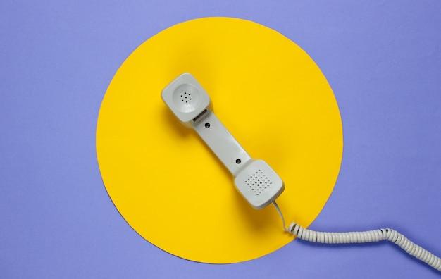 노란색 동그라미와 보라색에 레트로 전화 송수화기