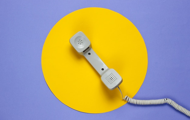 Retro telephone handset on a purple with a yellow circle