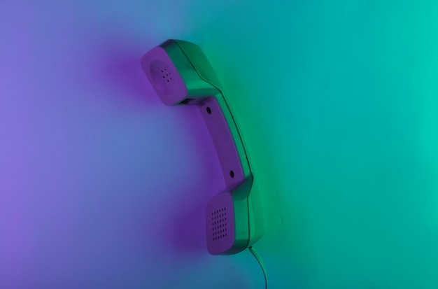 Retro telephone handset with green and magenta neon light