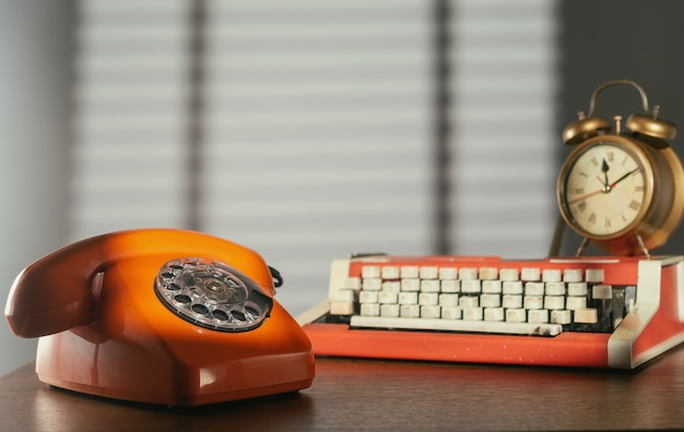 Retro telephone, typewriter and alarm clock on the table