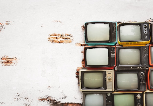 Retro televisions pile on floor in old room with white wall