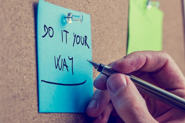 青いリマインダーの上にペンを持っている男の手をレトロに、木の板に固定して、自分のやり方でそれを行うためのインスピレーションを与えるアドバイスを添えて