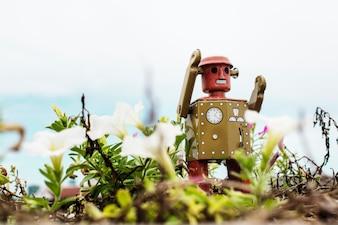 Retro tin robot toy playing in the garden