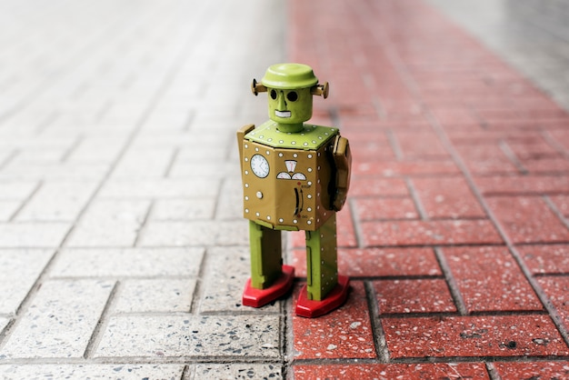 Retro tin robot toy standing on ground with pattern