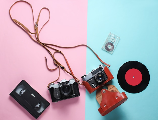 レトロなトップビュー静物。ブルーピンクのビニールレコード、ビンテージフィルムカメラ、ビデオ、オーディオカセット。フラット横たわっていた。上面図