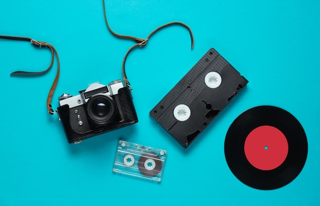 Retro top view still life. vinyl record, vintage film camera, video and audio cassette on blue. flat lay