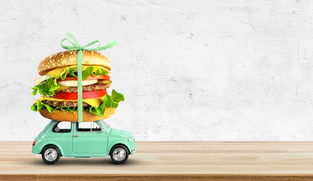 Retro toy car delivering fast food order on wooden table copy space