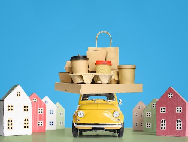 Ретро игрушечный автомобиль, доставляющий заказ еды на крыше. копировать пространство