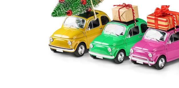 복고풍 장난감 자동차는 흰색 배경에 격리된 지붕에 크리스마스 트리와 선물을 들고 있는 이름이 없습니다. 크리스마스 배경입니다. 휴일 카드입니다. 공간을 복사합니다.