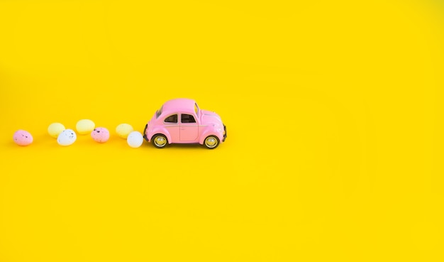 Retro toy pink car with easter egg on the roof. easter card with space for text on a yellow background.