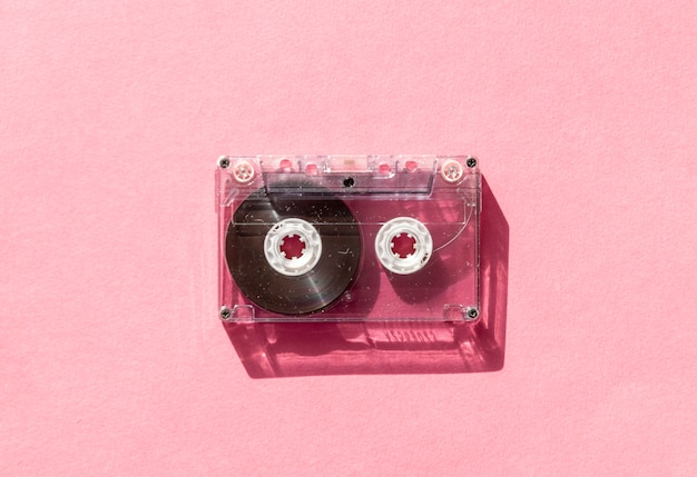 Retro transparent audio cassette tape on pink background. vintage music technology