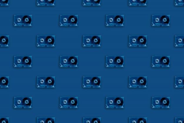 レトロな透明なオーディオカセットのシームレスなパターンは、トレンディなクラシックブルーの色です。ヴィンテージ音楽テクノロジー
