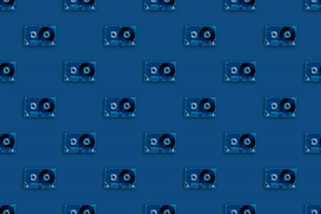 Retro transparent audio cassettes seamless pattern colored in trendy classic blue color. vintage music technology