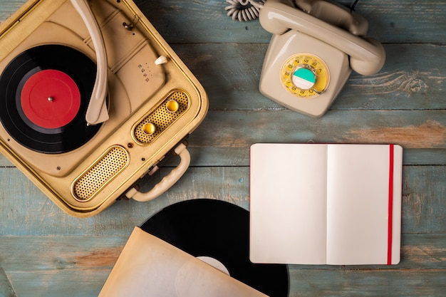 Retro turntable, notebook and telephone on wooden
