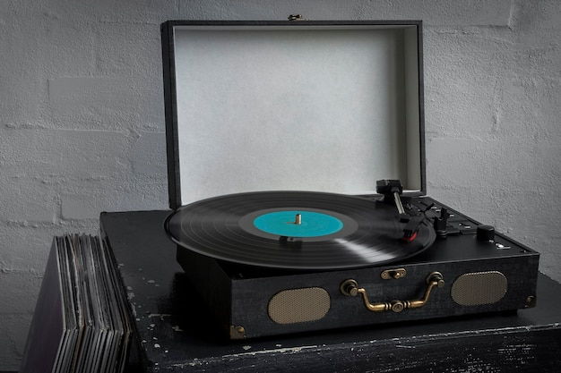 Retro turntable with playing vinyl disc and stack of records