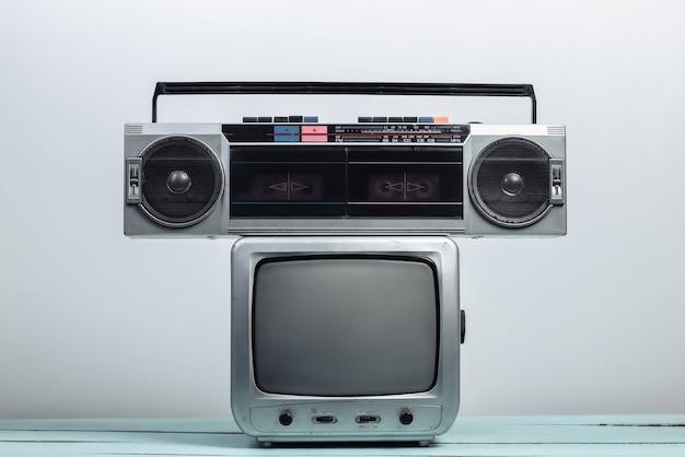 白い壁にオーディオテープレコーダーを備えたレトロなテレビ受信機。レトロメディア