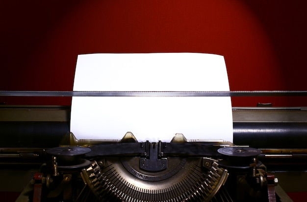 Retro typewriter and blanc paper on red background.