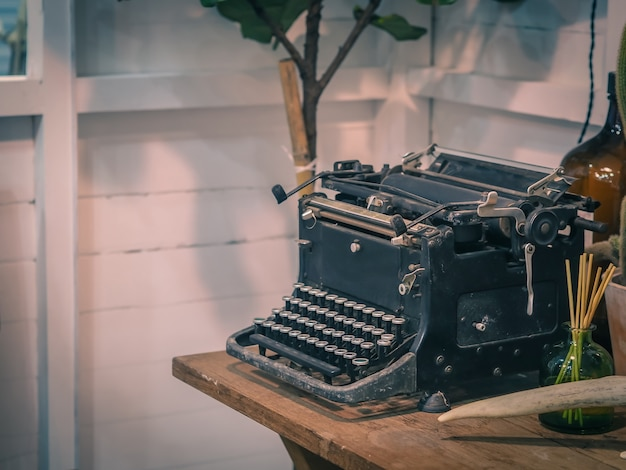 Retro typewriter on wooden table, vintage filter effect